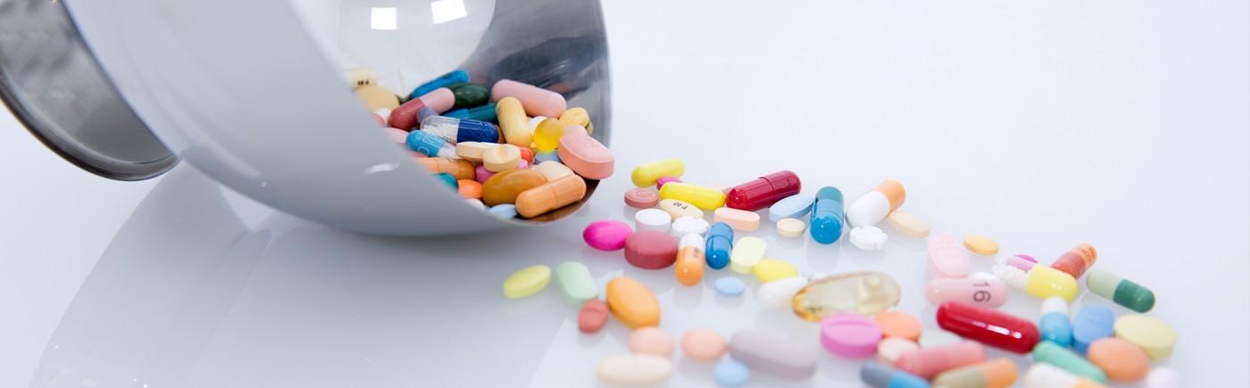 Verschiedene bunte Kapseln und Tabletten, die aus einer Patene auf eine Milchglasplatte geleert werden