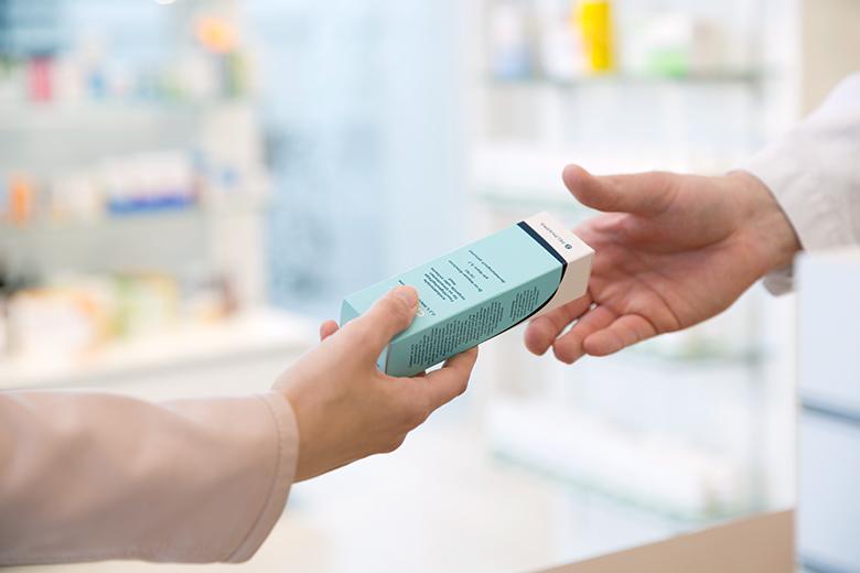 eine Apothekerin übergibt ein Medikament an den Patienten